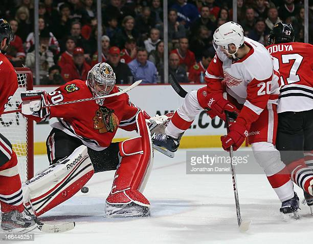 Drew Miller of the Detroit Red Wings attempts a shot against Corey Crawford of the Chicago Blackhawks at the United Center on April 12 2013 in...