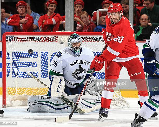 Drew Miller of the Detroit Red Wings tries to tip the puck as his brother and goalie Ryan Miller of the Vancouver Canucks tries to locate it during a...