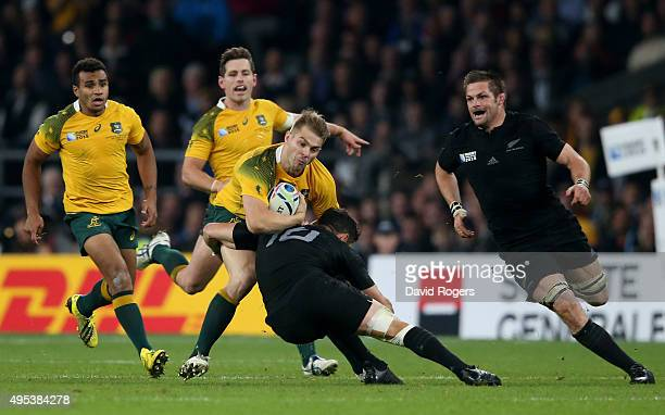 Drew Mitchell of Australia is tackled by Dan Carter of New Zealand during the 2015 Rugby World Cup Final match between New Zealand and Australia at...