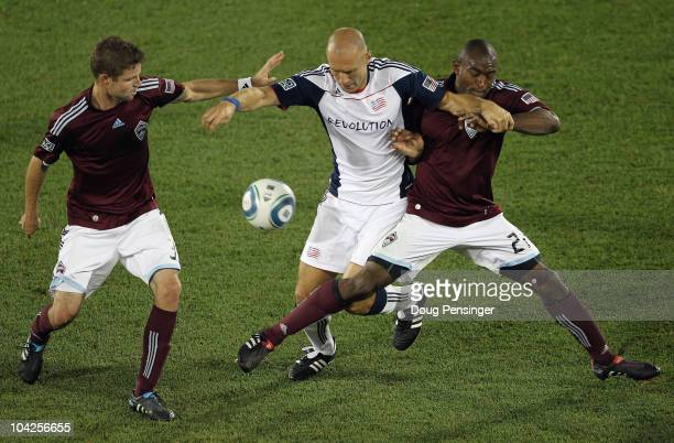 Drew Moor and Marvell Wynne of the Colorado Rapids try to protect the ball from Ilija Stolica of the New England Revolution at Dick's Sporting Goods...