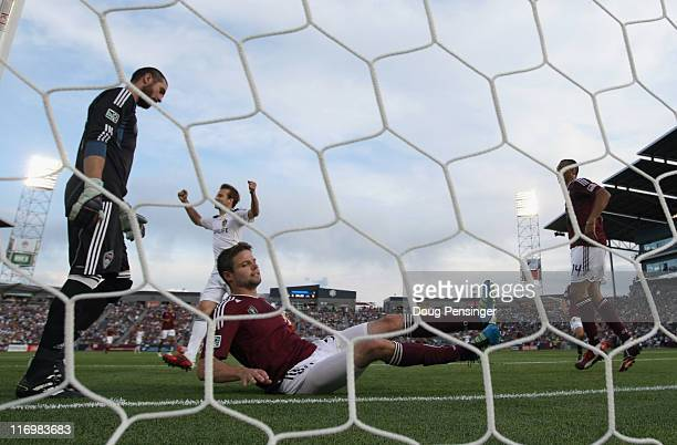 Drew Moor of the Colorado Rapids sits on the turf after scoring an own goal in the 25th minute as Mike Magee of the Los Angeles Galaxy celebrates as...