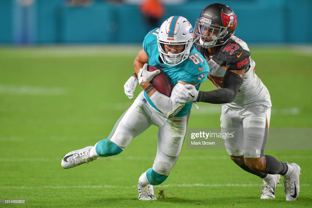 Drew Morgan #81 of the Miami Dolphins makes a catch as he is tackled by Javien Elliott of the Tampa Bay Buccaners in the third quarter during a preseason game against the Tampa Bay Buccaneers at Hard Rock Stadium on August 9, 2018 in Miami, Florida.