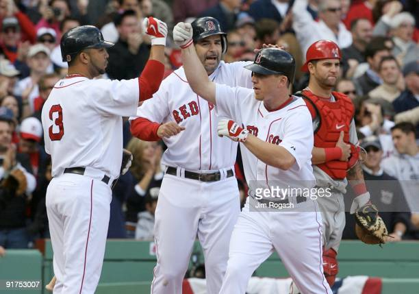 JD Drew of the Boston Red Sox celebrates with teammates Alex Gonzalez and Mike Lowell as Mike Napoli of the Los Angeles Angels of Anaheim looks on...