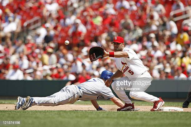 JD Drew of the Dodgers slides back into first base as Albert Pujols takes the throw during action between the Los Angeles Dodgers and St Louis...