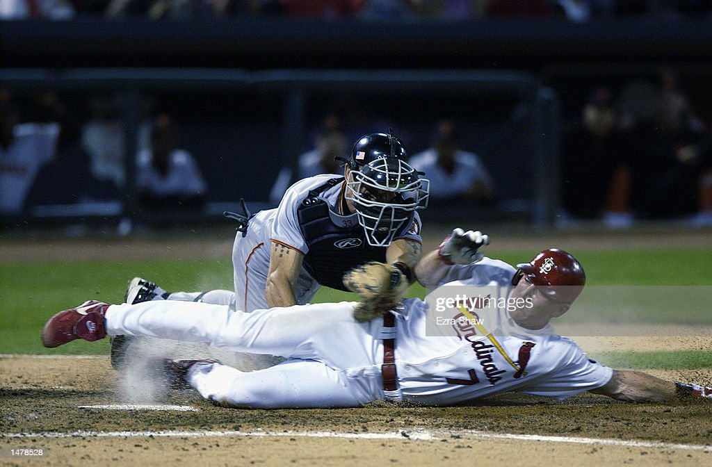 J.D. Drew of the St. Louis Cardinals is tagged out at the plate by Benito Santiago of the San Francisco Giants on October 10, 2002 during Game 2 of the NLCS at Busch Stadium in St. Louis, Missouri. The Giants won 4-1.