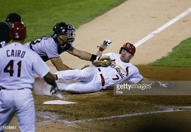 D Drew of the St Louis Cardinals slides as catcher Benito Santiago of the San Francisco Giants tags him out during the third inning in game two of...
