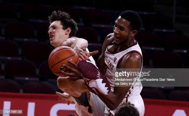 Drew Peterson and teammate Evan Mobley of the USC Trojans goes up for the rebound against the Utah Utes In the second half of a NCAA basketball game...