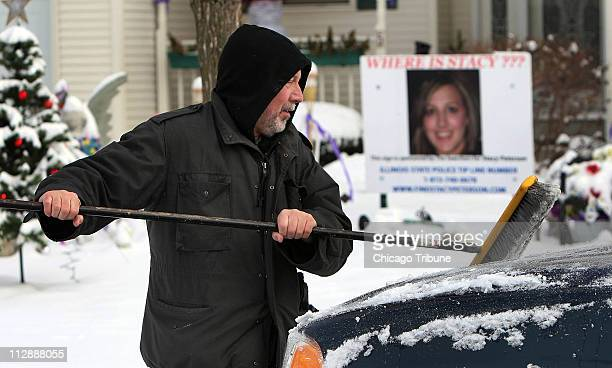 Drew Peterson cleans the snow from one of his vehicles in front of his home Wednesday December 17 in Bolingbrook Illinois Peterson who is still...
