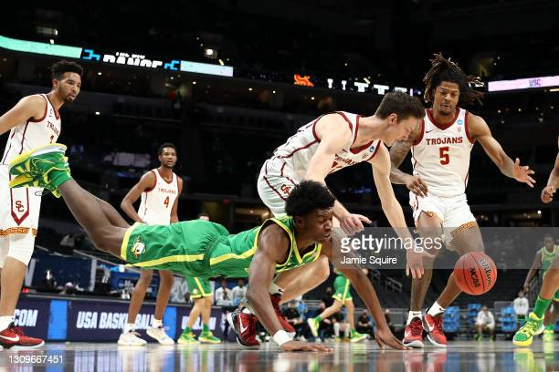 Drew Peterson of the USC Trojans and Eric Williams Jr. #50 of the Oregon Ducks dives for a loose ball in the first half of their Sweet Sixteen round...