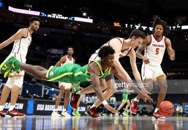 Drew Peterson of the USC Trojans and Eric Williams Jr. #50 of the Oregon Ducks dive for a loose ball in the first half of their Sweet Sixteen round...