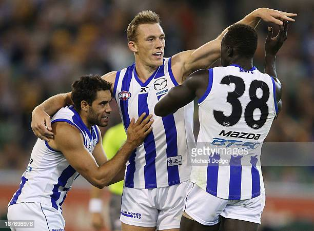 Drew Petrie celebrates a goal with Daniel Wells and Majak Daw of the Kangaroos during the round five AFL match between the Hawthorn Hawks and the...
