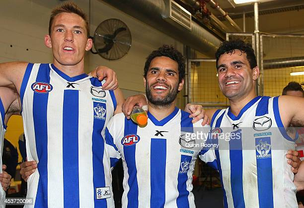 Drew Petrie Daniel Wells and Lindsay Thomas of the Kangaroos sing the song in the rooms after winning the round 21 AFL match between the North...