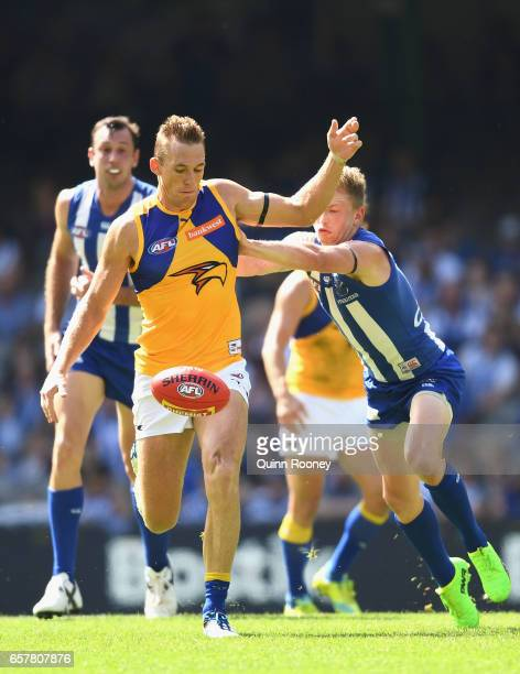 Drew Petrie of the Eagles kicks whilst being tackled by Jack Ziebell of the Kangaroos during the round one AFL match between the North Melbourne...
