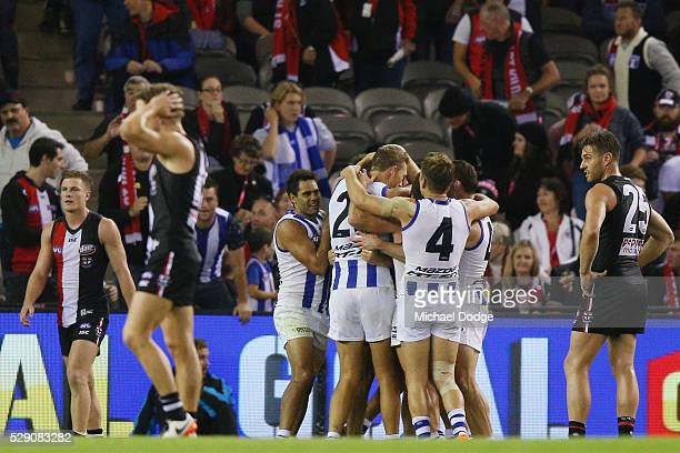 Drew Petrie of the Kangaroos celebrates on the final siren with teammates after winning his 300th match during the round seven AFL match between the...