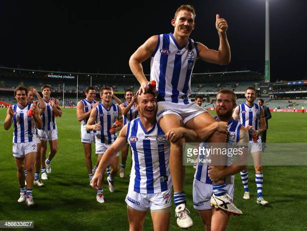 Drew Petrie of the Kangaroos is chaired from the ground by Brent Harvey and Leigh Adams after playimng his 250th AFL game during the round six AFL...