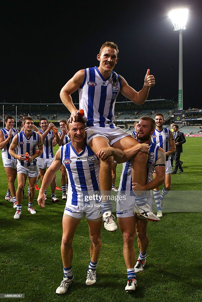 Drew Petrie of the Kangaroos is chaired from the ground by Brent Harvey and Leigh Adams after playimng his 250th AFL game during the round six AFL match between the Fremantle Dockers and the North Melbourne Kangaroos at Patersons Stadium on April 25, 2014 in Perth, Australia.