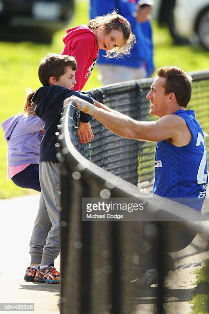 Drew Petrie of the Kangaroos, not to be re-contracted for next season by the club, talks with his kids during a North Melbourne Kangaroos AFL...
