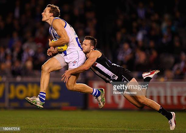 Drew Petrie of the Kangaroos takes a mark as Nathan Brown of the Kangaroos attempts to spoil during the round 21 AFL match between the Collingwood...