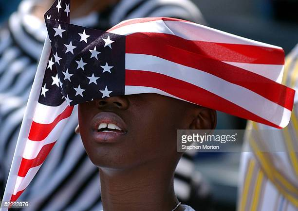 Drew Richardson tires to looks through an American flag February 20, 2005 during a homecoming celebration for 150 soldiers from the Army's 3rd...