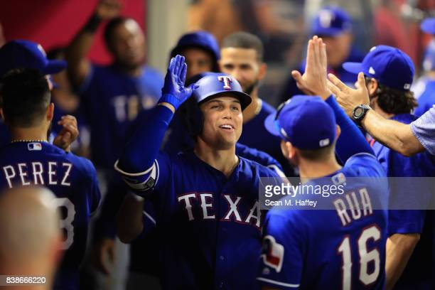 Drew Robinson is congratulated by Ryan Rua of the Texas Rangers after hitting a tworun homerun during the third inning of a game at Angel Stadium of...