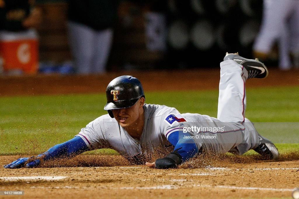 Drew Robinson #18 of the Texas Rangers dives into home plate to score a run against the Oakland Athletics during the fifth inning at the Oakland Coliseum on April 2, 2018 in Oakland, California. The Oakland Athletics defeated the Texas Rangers 3-1.