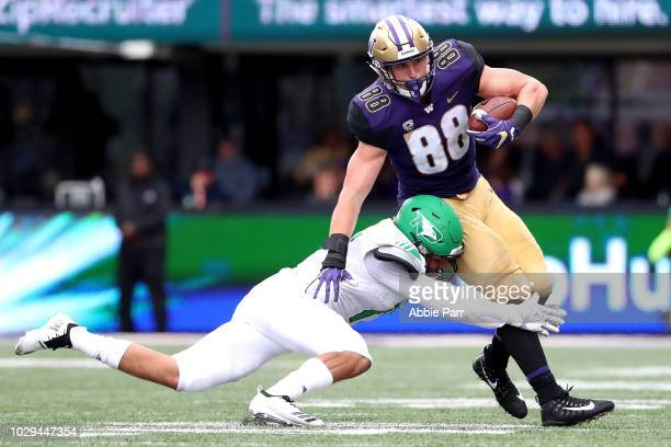 Drew Sample of the Washington Huskies is tackled by Jaxson Turner of the North Dakota Fighting Sioux in the second quarter during their game at Husky...