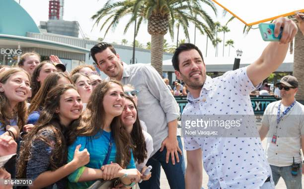 """Drew Scott and Jonathan Scott takes a selfie with fans at """"Extra"""" at Universal Studios Hollywood on July 17, 2017 in Universal City, California."""
