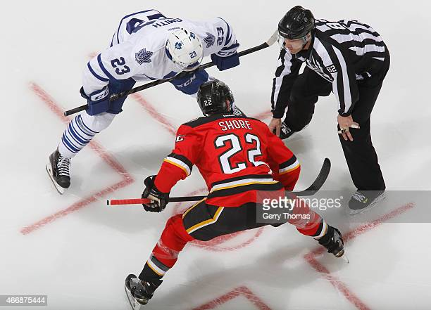 Drew Shore of the Calgary Flames faces off against Trevor Smith of the Toronto Maple Leafs at Scotiabank Saddledome on March 13 2015 in Calgary...
