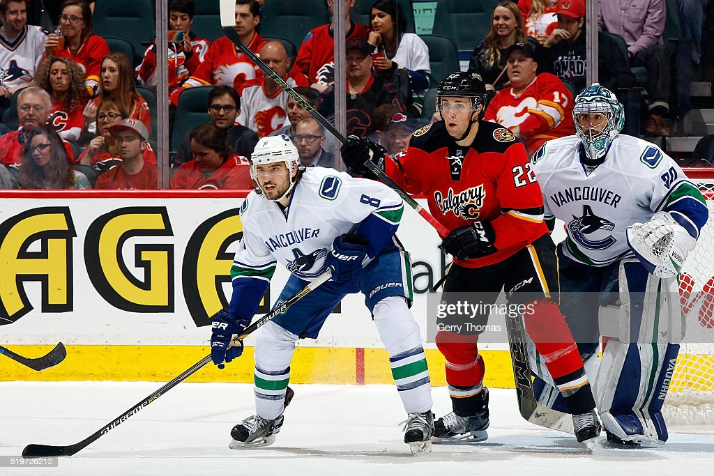 Drew Shore #22 of the Calgary Flames skates against Chris Tanev #8 of the Vancouver Canucks during an NHL game on April 7, 2016 at the Scotiabank Saddledome in Calgary, Alberta, Canada.