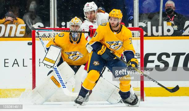 Drew Shore of the Carolina Hurricanes battles in front of the net against Jeremy Davies and Pekka Rinne of the Nashville Predators during the second...