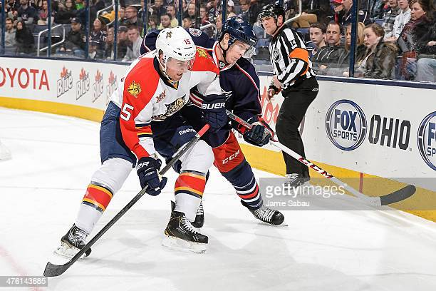 Drew Shore of the Florida Panthers and Matt Calvert of the Columbus Blue Jackets battle for position while chasing after a loose puck on March 1 2014...