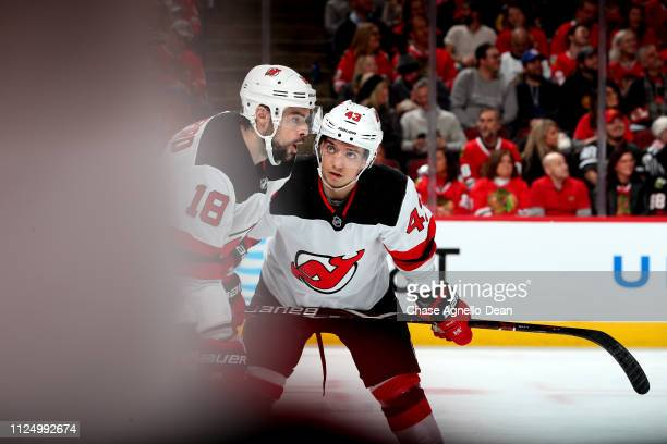Drew Stafford and Brett Seney of the New Jersey Devils talk in the second period against the Chicago Blackhawks at the United Center on February 14...