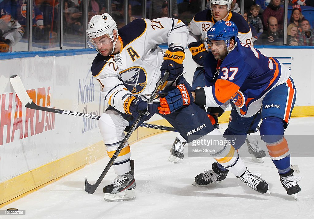 Drew Stafford #21 of the Buffalo Sabres protects the puck against Brian Strait #37 of the New York Islanders at Nassau Veterans Memorial Coliseum on February 9, 2013 in Uniondale, New York.