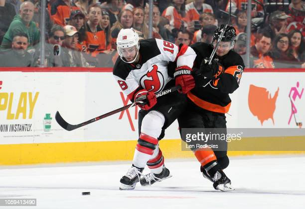 Drew Stafford of the New Jersey Devils battles for the puck against Scott Laughton of the Philadelphia Flyers on October 20 2018 at the Wells Fargo...