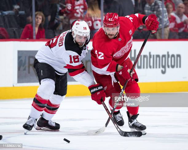 Drew Stafford of the New Jersey Devils battles for the puck with Martin Frk of the Detroit Red Wings during an NHL game at Little Caesars Arena on...