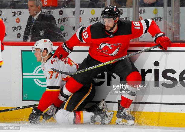 Drew Stafford of the New Jersey Devils in action against Mark Jankowski of the Calgary Flames on February 8 2018 at Prudential Center in Newark New...