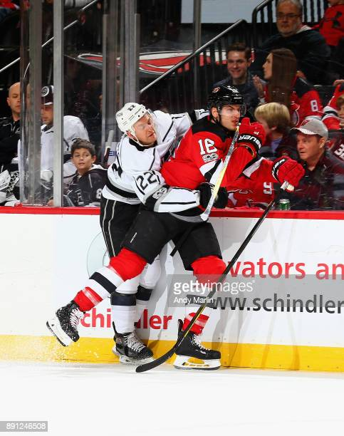 Drew Stafford of the New Jersey Devils is held at the boards by Trevor Lewis of the Los Angeles Kings during the game at Prudential Center on...