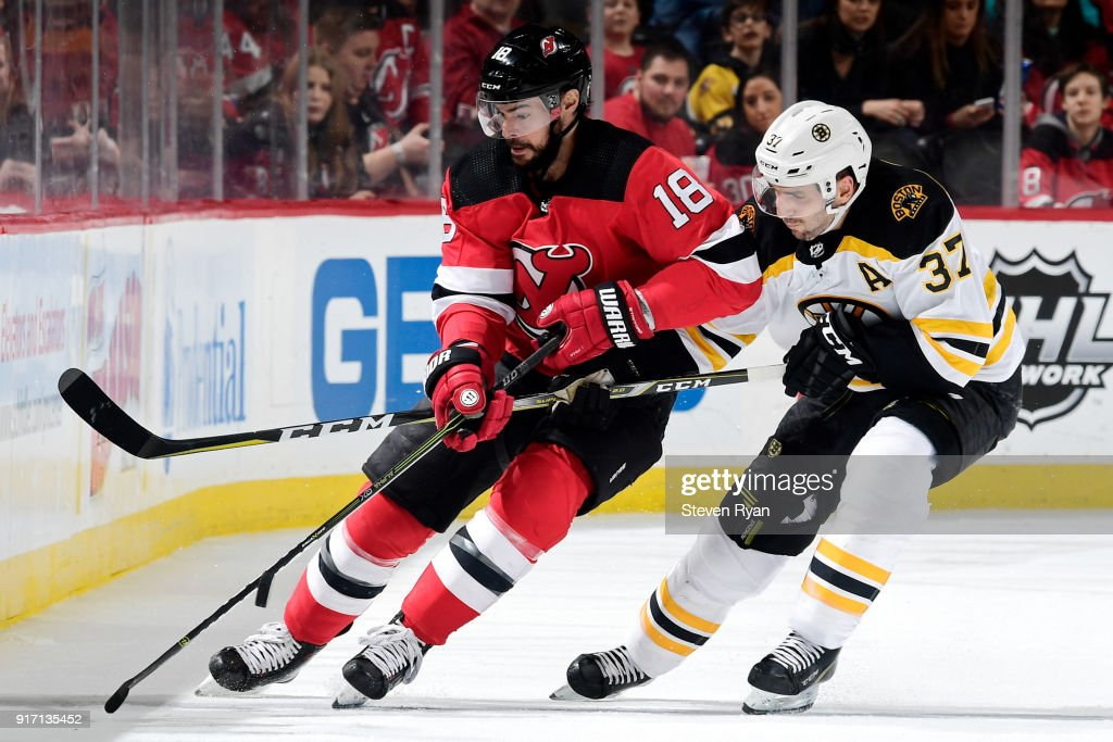 Drew Stafford #18 of the New Jersey Devils is pursued by Patrice Bergeron #37 of the Boston Bruins at Prudential Center on February 11, 2018 in Newark, New Jersey. The Boston Bruins defeated the New Jersey Devils 5-3.