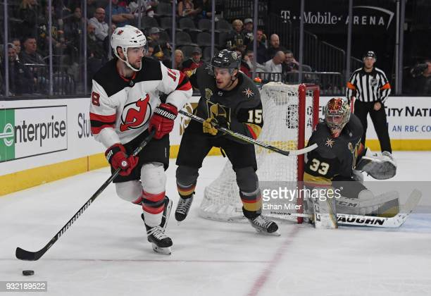 Drew Stafford of the New Jersey Devils skates with the puck against Jon Merrill of the Vegas Golden Knights as Maxime Lagace of the Golden Knights...