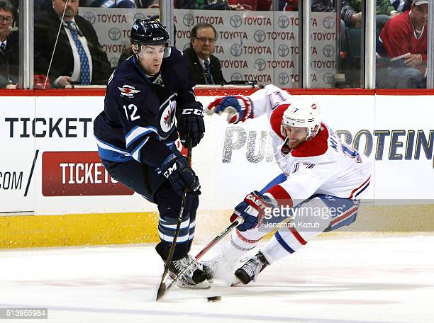 Drew Stafford of the Winnipeg Jets and Torrey Mitchell of the Montreal Canadiens battle for the loose puck during first period action at the MTS...