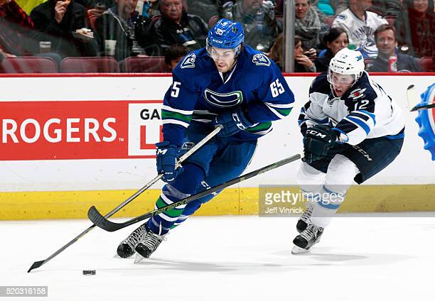 Drew Stafford of the Winnipeg Jets checks Alexandre Grenier of the Vancouver Canucks during their NHL game at Rogers Arena March 14 2016 in Vancouver...