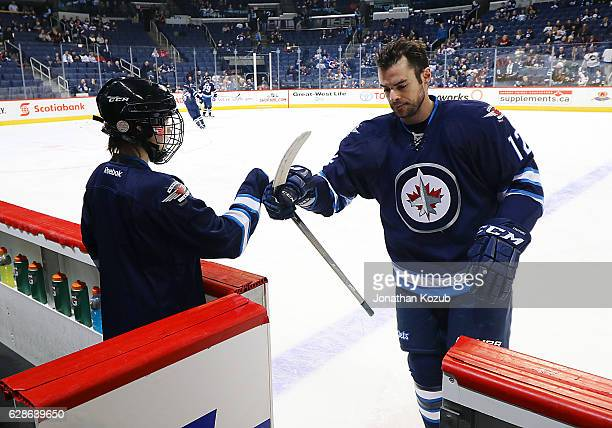 Drew Stafford of the Winnipeg Jets fist bumps the Toyota Trainer of the Day as he leaves the ice following the pregame warm up prior to NHL action...