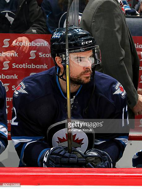Drew Stafford of the Winnipeg Jets looks on from the bench prior to puck drop against the Colorado Avalanche at the MTS Centre on December 18 2016 in...