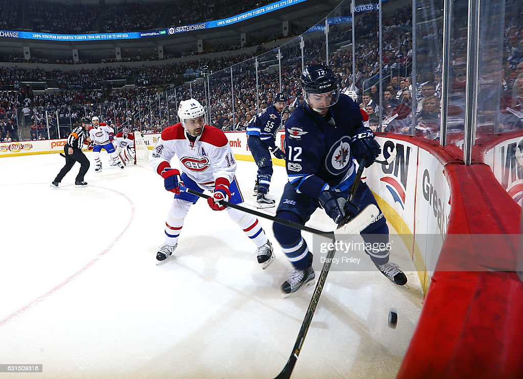 Drew Stafford #12 of the Winnipeg Jets plays the puck along the boards as Tomas Plekanec #14 of the Montreal Canadiens gives chase during first period action at the MTS Centre on January 11, 2017 in Winnipeg, Manitoba, Canada.