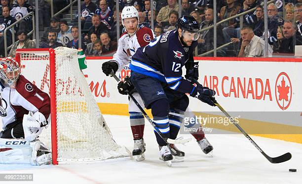 Drew Stafford of the Winnipeg Jets plays the puck behind the as Mikhail Grigorenko of the Colorado Avalanche defends during thirdperiod action at the...