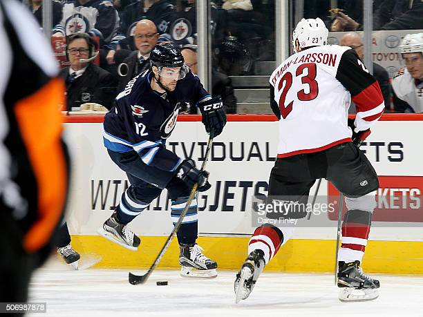 Drew Stafford of the Winnipeg Jets plays the puck down the ice as Oliver EkmanLarsson of the Arizona Coyotes defends during first period action at...