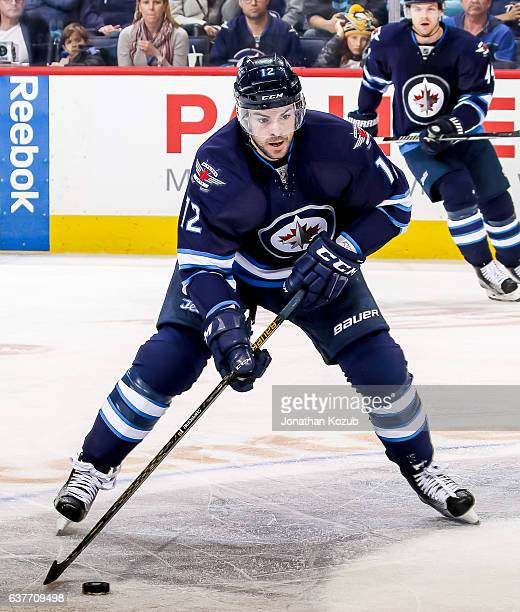Drew Stafford of the Winnipeg Jets plays the puck down the ice during third period action against the New York Islanders at the MTS Centre on...