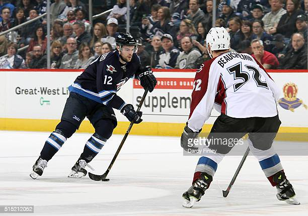 Drew Stafford of the Winnipeg Jets plays the puck up the ice as Francois Beauchemin of the Colorado Avalanche defends during first period action at...