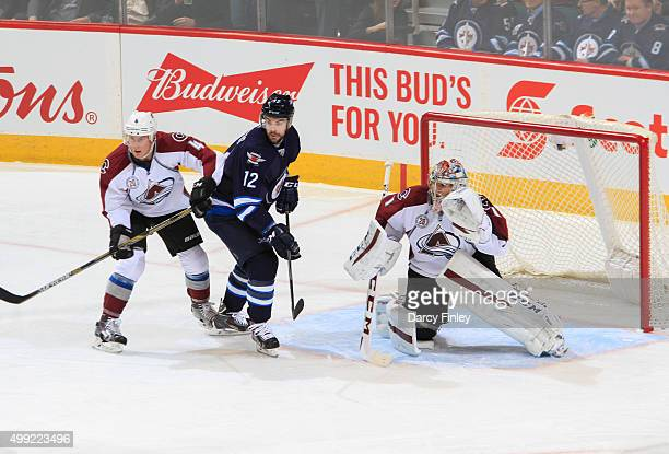 Drew Stafford of the Winnipeg Jets positions himself between Tyson Barrie and goaltender Semyon Varlamov of the Colorado Avalanche as they keep an...