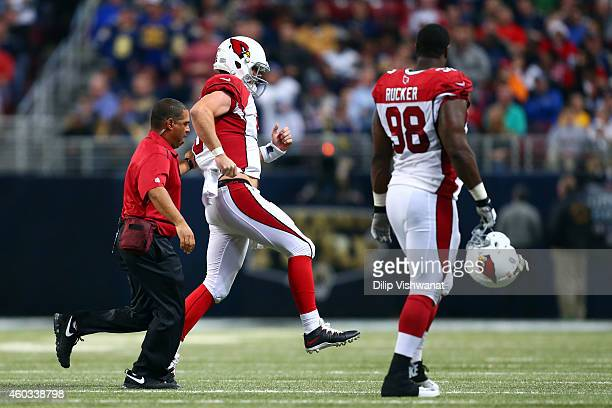 Drew Stanton of the Arizona Cardinals hobbles off the field after being sacked by Aaron Donald of the St Louis Rams in the third quarter during their...
